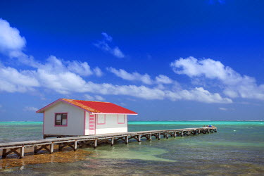 BLZ0109AW Central America, Belize, Ambergris Caye, San Pedro, a red hut on a jetty contrasted against the blue sky and turquoise Caribbean sea