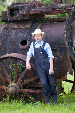 BLZ0153AW Central America, Belize, Orange Walk district, Hill Bank Field Station, a Mennonite boy leaning against and old British traction engine on a traditional Mennonite carriage