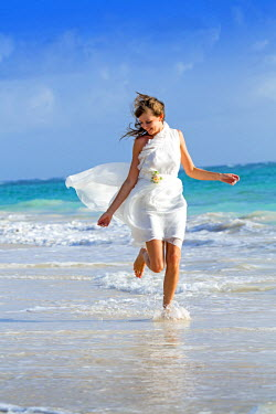 DMR0011AW Caribbean, Dominican Republic, La Altagracia province, Punta Cana, Bavaro, Beautiful young woman in a wedding dress running through the waves on the beach with a turquoise Atlantic behind (MR)