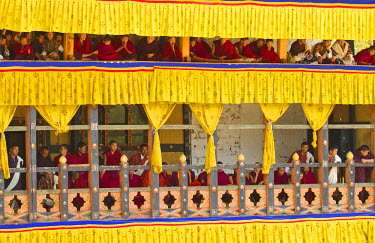 BHU1859AW Asia, Paro Dzong, Paro, Bhutan. Monks watching the dancing and celebrations at the Paro Festival from their special seating platform high above the courtyard.