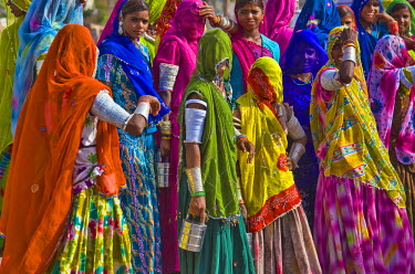IND7494AW Asia, India, Rajasthan State, Jodhpur. Women in traditional colourful Indian saris, arm bangles and bracelets wait on a street corner to be collected and taken to their place of work. Many women in ru...