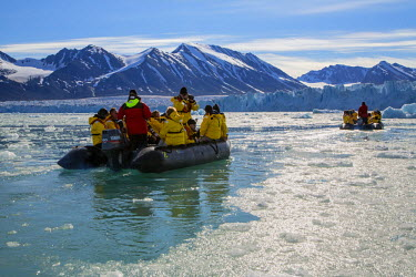 NOR0657 Norway, Arctic, Svalbard, Spitzbergen, Liefdefjorden. Visitors riding in zodiacs forge a way through brash ice towards the spectacular Monaco Glacier.