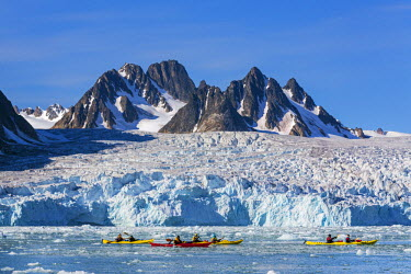NOR0665 Norway, Arctic, Svalbard, Spitzbergen, Liefdefjorden. Visitors in kayaks paddle in brash ice past the magnificent Monaco Glacier which lies at the end Liefdefjorden, northern Spitzbergen.