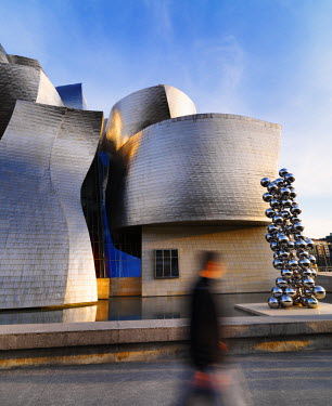 SPA5046AW Spain, Bilbao, Guggenheim museum at with man walking past.