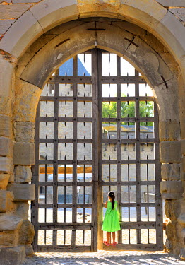 FRA7951AW France, Languedoc, Carcassonne, Girl looking through castle gate (MR)