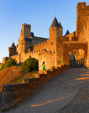 FRA7955AW France, Languedoc, Carcassonne, girl walking on wall to Aude gate (MR)