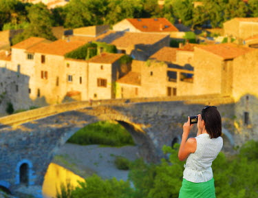 FRA7968AW France, Languedoc, Lagrasse, woman photographing bridge (MR)