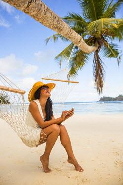 SC01145 Woman texting on a smart phone on the beach on Mahe, Seychelles