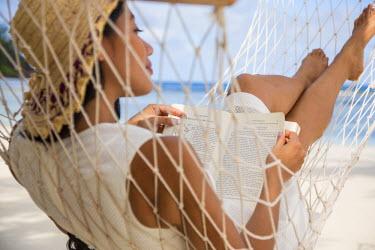 SC01150 Woman reading a book on a hammock on a beach on Mahe, Seychelles