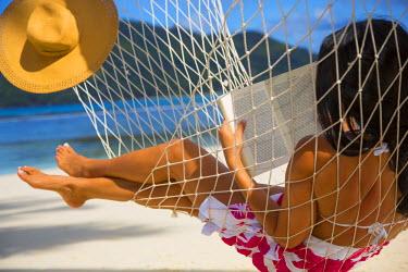 SC01160 Woman reading a book on a hammock on a beach on Mahe, Seychelles