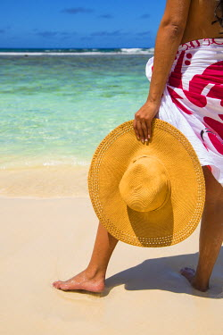 SC01173 Young woman holding summer hat on beach, Mahe, Seychelles