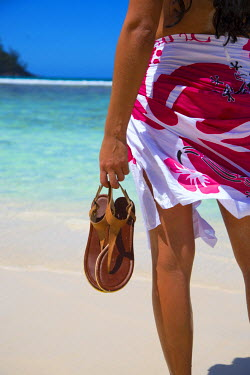 SC01174 Young woman holding sandals, Mahe, Seychelles