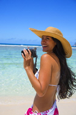 SC01178 Young woman with camera on the beach, Mahe, Seychelles