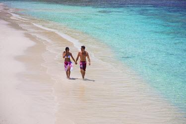 SC01181 Couple walking along the beach, Mahe, Seychelleshands