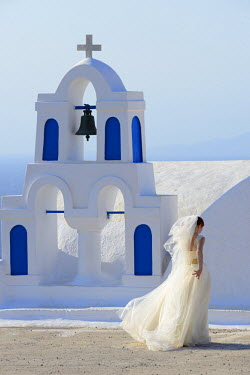 GRE0603AW Bride walking past church, Santorini, Kyclades, South Aegean, Greece, Europe