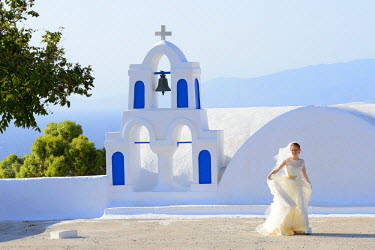 GRE0604AW Bride walking past church, Santorini, Kyclades, South Aegean, Greece, Europe
