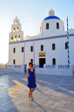 GRE0632AW Woman in blue dress in Oia, Santorini, Kyclades, South Aegean, Greece, Europe