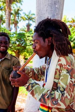 AF02ALA0009 Africa, Angola, Benguela. Portrait of Rastafarian man smoking.