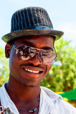 AF02ALA0014 Africa, Angola, Benguela. Portrait of young man in hat and sunglasses.