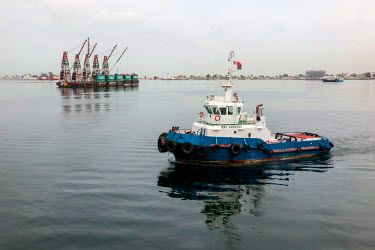 AF02ALA0101 Africa, Angola, Luanda. Tug boat near barge.