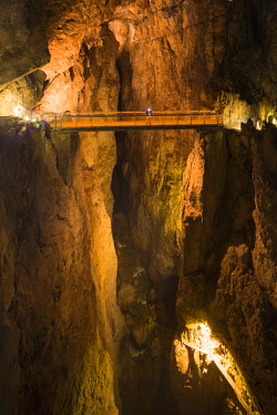 SLO1080AW Slovenia, Karst Region, Skocjan Caves Park. A man stands on the Cerkvenik Bridge looking down at the Reka River. The last major flood was in 1965 when the river flooded 10 metres above the height of t...