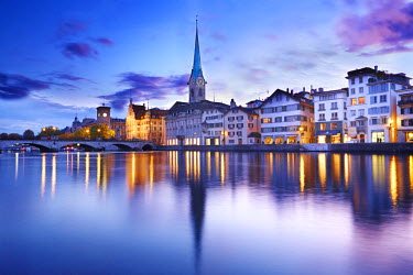 SWI7296AW Europe, Switzerland, Zurich, a night time view of the clocktower of Fraumunster cathedral and the Stadthaus (to the church's left) reflected the Limmat river in the old city centre