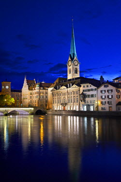 SWI7297AW Europe, Switzerland, Zurich, a night time view of the clocktower of Fraumunster cathedral and the Stadthaus (to the church's left) reflected the Limmat river in the old city centre