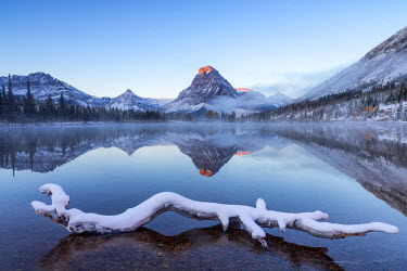 US27CHA2895 Sinopah Mountain reflects into Pray Lake in the Two Medicine Valley after fresh snowfall in Glacier National Park, Montana, USA