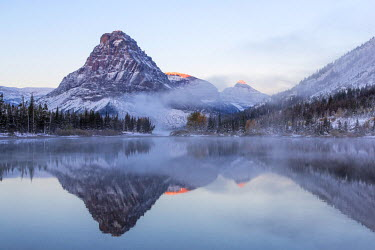 US27CHA2896 Sinopah Mountain reflects into Pray Lake in the Two Medicine Valley after fresh snowfall in Glacier National Park, Montana, USA