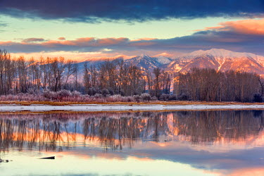 US27CHA2931 Swan Mountains reflect into the Flathead River at sunset near Kalispell, Montana, USA