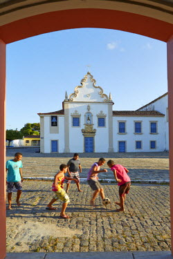 BRA2179AW South America, Brazil, North East, Sergipe, Sao Cristovao, children playing street football in front of the 17rh Century baroque Carmelite convent (Convento do Carmo)