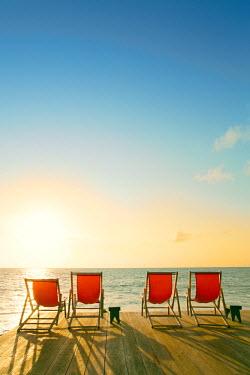 BRA2188AW South America, Brazil, Alagoas, Praia do Patacho, sun loungers on a deck overlooking the beach and the sun rising over the Atlantic PR