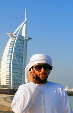 AS44BBA0054 Man with mobile phone talking in front of world's only 7-star hotel, the Burj Al Arab, in Dubai, United Arab Emirates.