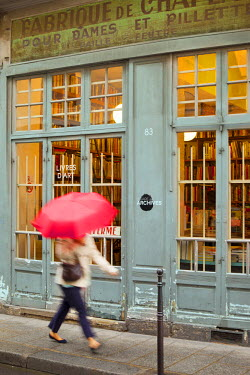 EU09BJN0885 Woman with pink umbrella walks past a bookstore in historic Marais district, Paris, France