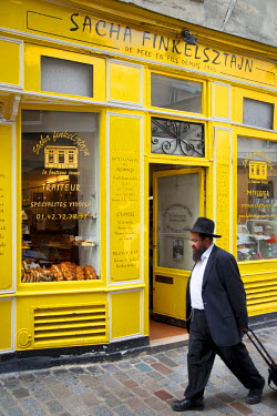 EU09BJN0948 Orthodox Jew walks past historic Yiddish bakery Finelsztajn in the Marais, Paris, France.