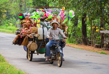 CMB1369 Cambodia, Siem Reap, Siem Reap Province. A travelling salesman and his shop on a motorcycle trailer on the outskirts of Siem Reap
