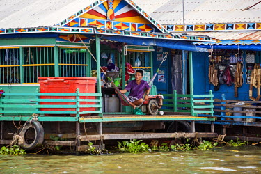 CMB1379 Cambodia, Tonle Sap, Siem Reap Province. A man rests on the veranda of his floating house beside a shop on Lake Tonle Sap. Lake Tonle Sap is Southeast Asia�s largest freshwater lake.