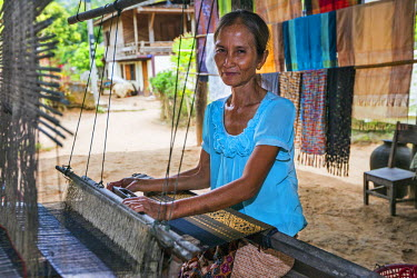 LAO1150 Laos, Ban Muangkeo, Luang Prabang, Luang Prabang Province. A woman weaves cloth of an intricate design on her wooden loom in the small village of Ban Muangkeo on the Mekong River, some 25km from Luang...