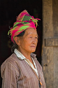 LAO1155 Laos, Oudomxay, Oudomxay Province. An H�mong woman at the entrance to her home.
