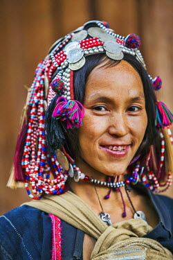 Laos, Muang La, Oudomxay Province. A woman from the minority Akha Puli wearing a headdress decorated with old French Indo-China silver coins. Her teeth are stained red by chewing betel nuts.