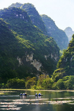 Vietnam, Ninh Binh Province, Tam Coc. Karst limestone mountains tower above visitors boating on a stretch of the Ngo Dong River.