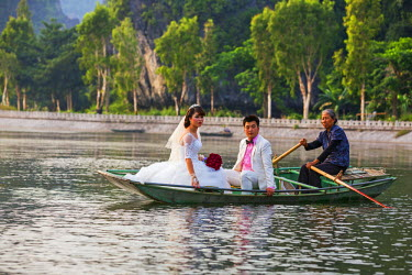 Vietnam, Ninh Binh Province, Tam Coc. A wedding couple boating on a stretch of the Ngo Dong River. The boats are typically rowed by women.