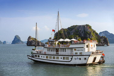 VIT0300 Vietnam, Quang Ninh Province, Ha Long Bay. A tourist junk cruising among the two thousand limestone Karst islands in Ha Long Bay - a spectacular World Heritage Site.