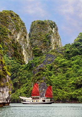 VIT0309 Vietnam, Quang Ninh Province, Ha Long Bay. A tourist junk anchored among spectacular limestone Karst islands in Ha Long Bay – a World Heritage Site of outstanding natural beauty.
