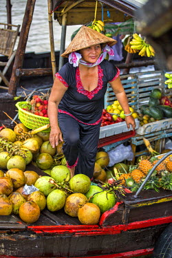 VIT0410 Vietnam, Cai Be, Mekong Delta. A lady selling fruit at the wholesale floating market of Cai Be.