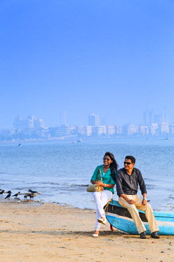 IND7528AW India, Maharashtra, Mumbai, Chowpatty Beach, a couple sitting on a fishing boat on Chowpatty beach with the skyscrapers of Mumbai city centre and Nariman point in the distance MR