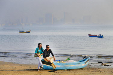 IND7529AW India, Maharashtra, Mumbai, Chowpatty Beach, a couple sitting on a fishing boat on Chowpatty beach with the skyscrapers of Mumbai city centre and Nariman point in the distance MR