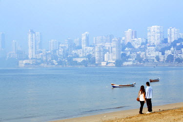 IND7539AW India, Maharashtra, Mumbai, Chowpatty Beach, a couple on Chowpatty beach with the skyscrapers of Mumbai city center in the distance MR