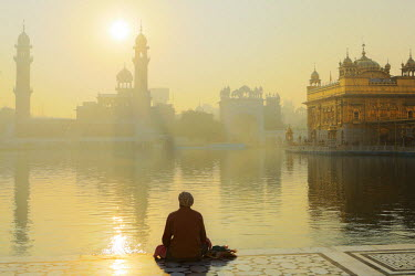 IND7569AW India, Punjab, Amritsar, a sikh pilgrim praying at the Golden Temple - the holiest shrine of Sikhism - with mist rising off the lake during a golden dawn