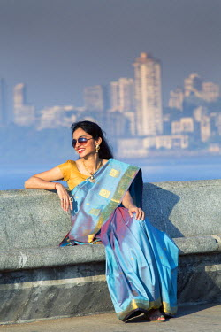 IND7589AW India, Maharashtra, Mumbai, a young Indian woman in a blue and gold saree wearing sunglasses and laughing sitting on the promenade on over Marine Drive in South Mumbai MR